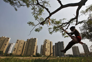 A boy plays on a swing suspended from a tree in front of a residential estate under construction in Kolkata