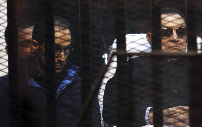 Former Egyptian President Hosni Mubarak listens next to his son Gamal inside a dock during his trial at the police academy on the outskirts of Cairo
