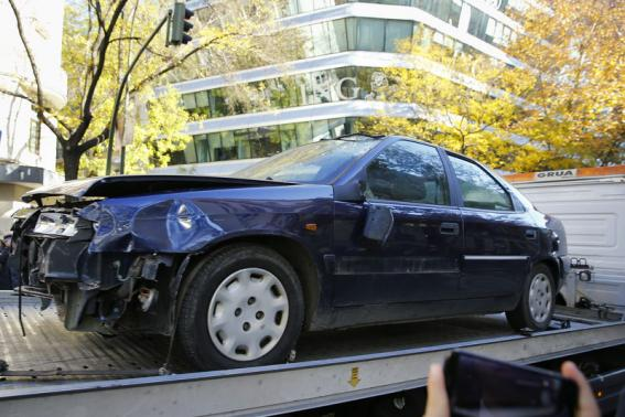 Car that was driven into the headquarters of Spain's ruling People's Party (PP) is towed away in Madrid