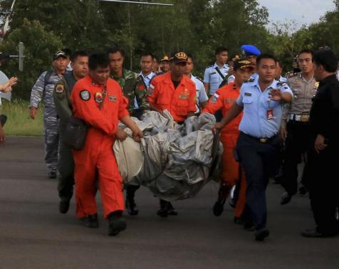 Members of the Search and Rescue Agency carry debris recovered from the sea presumed from missing Indonesia AirAsia flight QZ 8501 at Pangkalan Bun