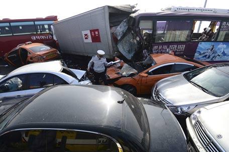 A policeman walks between damaged vehicles on Yeongjong Bridge in Incheon