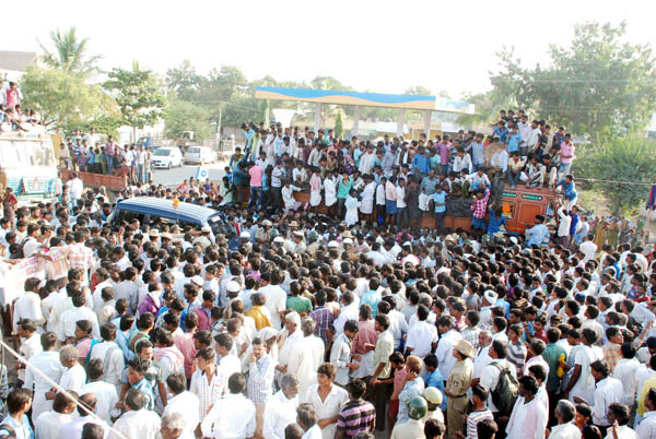 Crowd gather around the police vehicle while protesting following the absence of doctors and medical staff at the Primary Health Centre that led to the death of a BCM Hostel student who needed treatment after being electrocuted at a school in Potnal Village, Manvi, Raichur on Friday Dec 04 2015 - KPN ### Raichur: Death of Student due to electrocution