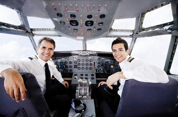Pilots sitting in an airplane cabin flying and smiling