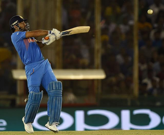 India's captain Mahendra Singh Dhoni plays a shot during the World T20 cricket tournament match between India and Australia at The Punjab Cricket Stadium Association Stadium in Mohali on March 27, 2016. / AFP / MONEY SHARMA (Photo credit should read MONEY SHARMA/AFP/Getty Images)