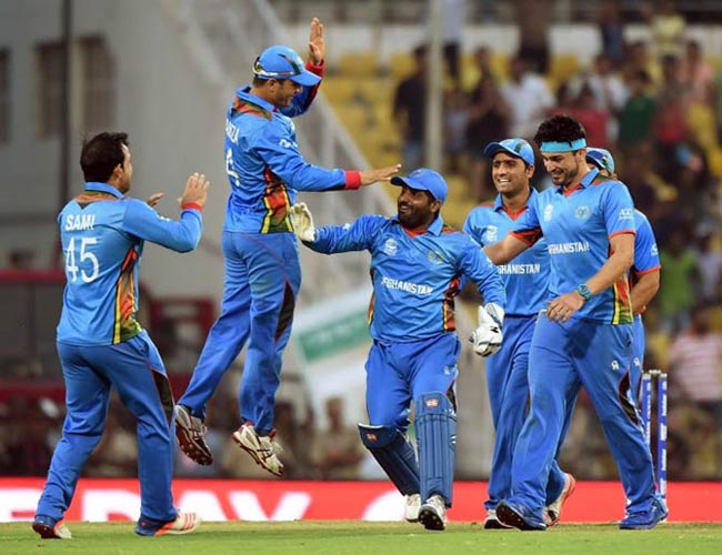 Afghanistan's players celebrate after the wicket of West Indies's batsman Andre Russell during the World T20 cricket tournament match between West Indies and Afghanistan at The Vidarbha Cricket Association Stadium in Nagpur on March 27, 2016. / AFP / PUNIT PARANJPE