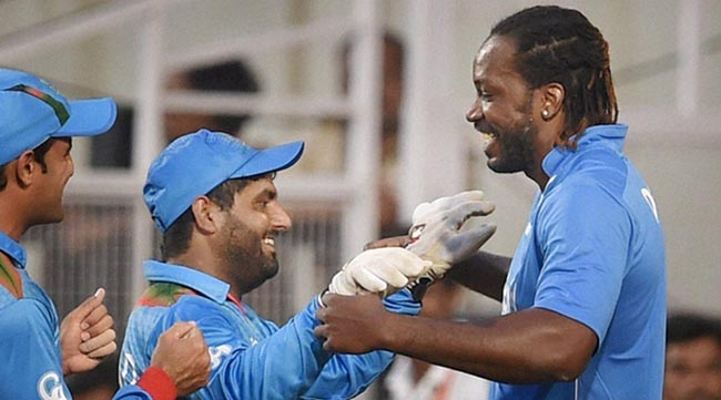 Nagpur: Afghanistan wicket keeper Mohammad Shahzad with West Indies player Chris Gayle after victory over West Indies during the ICC T20 World cup match played in Nagpur on Sunday. PTI Photo by Shashank Parade(PTI3_27_2016_000147A)
