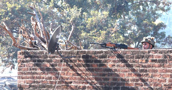 An Indian army soldier looks at an Indian air force chopper on a reconnaissance mission, as he takes position on a rooftop of a building outside the Indian airbase in Pathankot, 430 kilometers (267 miles) north of New Delhi, India, Saturday, Jan. 2, 2016. At least four gunmen entered an Indian air force base near the border with Pakistan on Saturday morning and exchanged fire with security forces, leaving two of them dead, officials said. (AP Photo/Channi Anand)