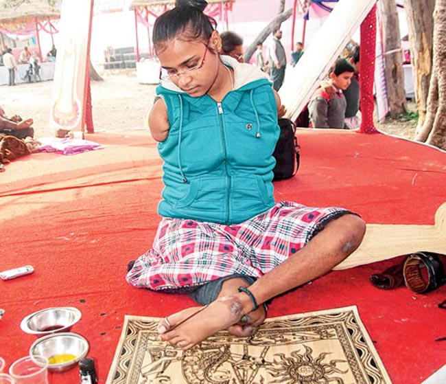 Sarita Dwivedi, who lost her right leg and two hands in an accident at the age of 4, busy in making a Madhubani painting in Shilpotsav, the  ongoing art exhibition organised by Upendra Maharathi Shilp Anusandhan Sansthan in Patna on Friday Pix by Nagendra Kumar Singh Story by Shuchi