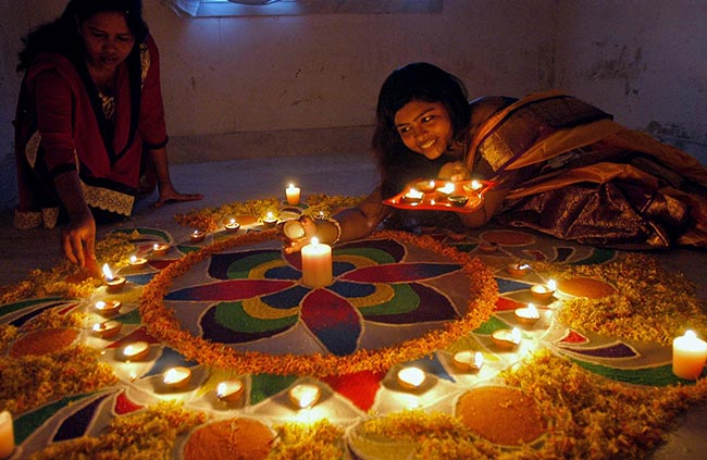 Kolkata: A girl makes a Rangoli ahead of Diwali in Kolkata, on Oct.21, 2014. (Photo: Kuntal Chakrabarty/IANS)