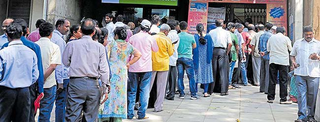People queue up outside an ATM to withdraw money at State Bank of Mysore Dr Ambedkar Veedi Branch, in Bengaluru on Saturday. -Photo/ Ranju P