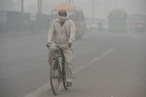 A cyclist covers his face while riding along a major road as smog covers the capital's skyline in New Delhi on November 2, 2016.  New Delhi's air quality has steadily worsened over the years, a consequence of rapid urbanisation that brings pollution from diesel engines, coal-fired power plants and industrial emissions. / AFP PHOTO / PRAKASH SINGH