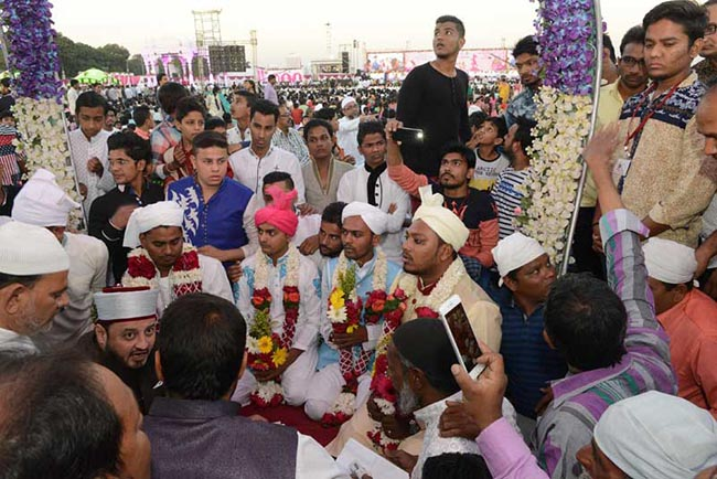 Five Indian Muslim grooms assemble at a mass wedding of 236 fatherless girls organised by the charitable PP Savani Group in Surat, some 270 km from Ahmedabad, on December 25, 2016. Out of 236 fatherless girls married in the mass wedding event, five were from the Muslim community, and one Christian, with the majority being Hindus.  / AFP PHOTO / SAM PANTHAKY